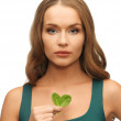 Woman with spinach leaves on palms — Stock Photo #18548883