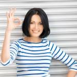 Happy teenage girl showing ok sign — Stock Photo #18725345