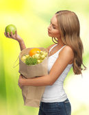 Woman with shopping bag full of fruits — Stock Photo