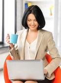 Businesswoman at home with laptop and cup — Stock Photo