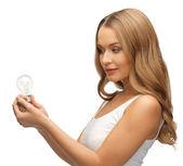 Woman with energy saving bulb — Stock Photo