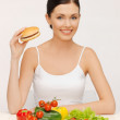 Woman with hamburger and vegetables — Stock Photo #19085341