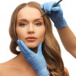 Woman face and beautician hands - Stok fotoraf