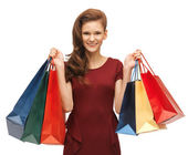Teenage girl in red dress with shopping bags — Stock Photo