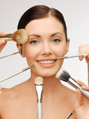 Beautiful woman with brushes — Stock Photo