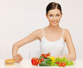 Woman with hamburger and vegetables — Stock Photo