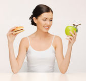 Woman with hamburger and apple — Stock Photo