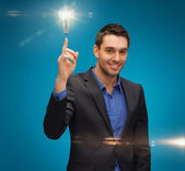 Man in suit with light bulb — Stock Photo