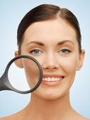 Woman with magnifying glass over acne — Stock Photo