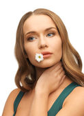 Woman with camomile in mouth — Stock Photo
