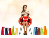Girl in red dress with shoes, bag and sale sign — Stock Photo