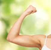 Sporty woman flexing her biceps — Stockfoto