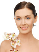 Lovely woman with orchid flower — Stock Photo