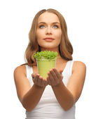 Woman with green grass in pot — Stock Photo