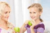 Mother and little girl with green apple — Stock Photo