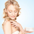 Beautiful woman with moisturizing creme — Stock Photo