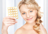Young woman with pills — Stockfoto