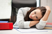 Bored and tired woman behid the table — Stock Photo