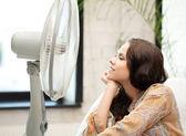 Felice e sorridente donna seduta vicino a ventilatore — Foto Stock