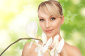 Beautiful woman with orchid flower and butterflies — Stock Photo