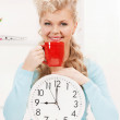 Royalty-Free Stock Photo: Attractive businesswoman with clock and red cup