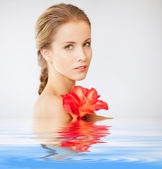 Lovely woman with lily flower in water — Stock Photo