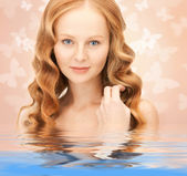 Beautiful woman with butterflies in water — Stock Photo