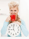 Attractive businesswoman with clock and red cup — Stock Photo