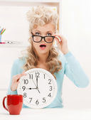 Wondering businesswoman with clock — Stock Photo