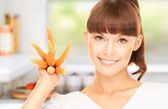 Housewife with carrots at the kitchen — Stock Photo