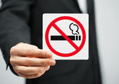 Man in suit holding no smoking sign — Stockfoto