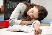 Bored and tired woman sleeping on the table — Stock Photo