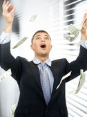 Businessman in money rain indoors — Stock Photo