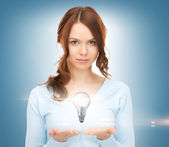 Woman showing light bulb on the palm of her hands — Stock Photo