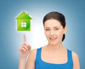 женщина указывая пальцем на зеленый дом — Стоковое фото