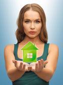 женщина, держащая зеленый дом в ее руках — Стоковое фото