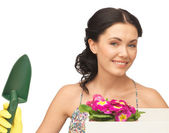 Housewife with flower in box and gardening trowel — Stock Photo