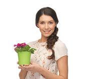 Prachtige huisvrouw met bloem in pot — Stockfoto