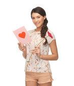 Mladá žena drží květinu a pohlednice — Stock fotografie