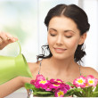 Housewife with flower in pot and watering can - Stock Photo