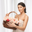 Woman with basket full of flowers — Stock Photo