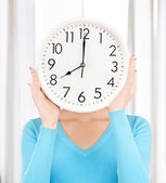 Businesswoman with clock over her face — Stock Photo