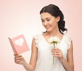 молодая женщина, держащая цветок и открытка — Стоковое фото