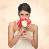 Woman smelling bouquet of flowers — Stock Photo