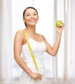 Mujer deportiva con manzana y cinta métrica — Foto de Stock