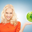 Woman holding green globe on her hand - Stock Photo