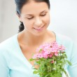 Lovely housewife with flower in pot — Stock Photo #23315622