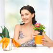 Housewife with flower in pot and gardening set — Stock Photo #23315764