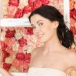 Woman with old ladder and background full of roses — Stock Photo #23317616