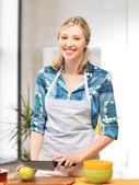 красивая женщина на кухне, резка яблоко — Стоковое фото